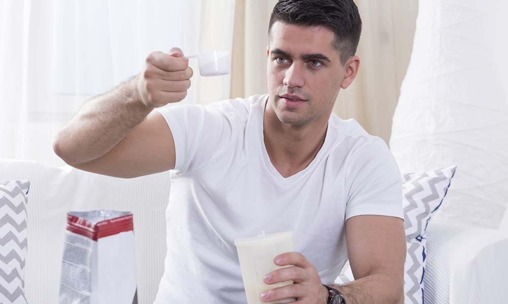 Handsome bodybuilder preparing protein shake before workout