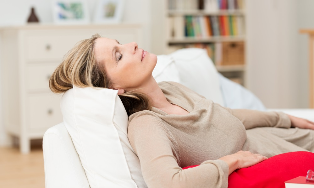 Woman having a nap on the sofa relaxing with her head tilted back on the cushion and eyes closed