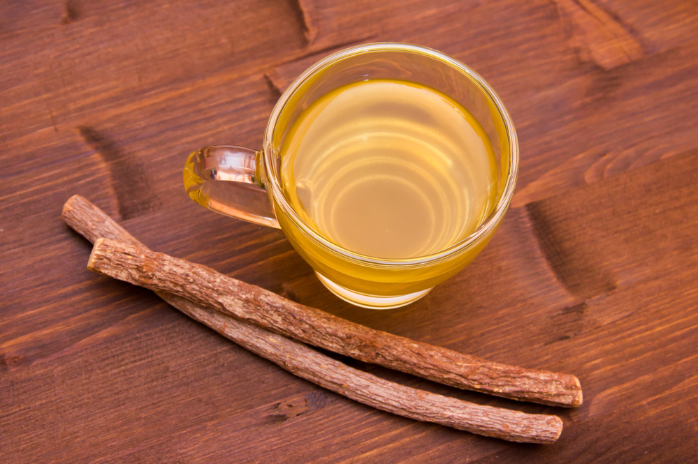 Cup of herbal tea licorice in wooden table top view